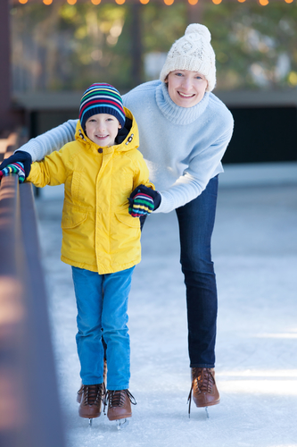 happy family of mother and her son enjoying ice skating together at winter at outdoor skating rink